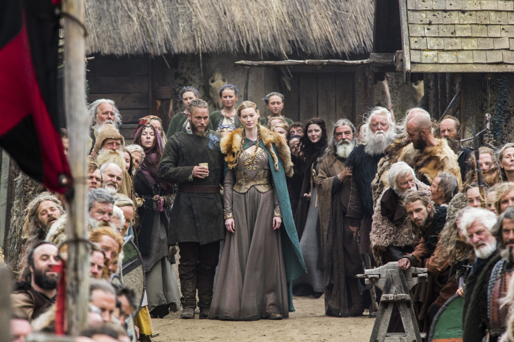 Earl Ragnar (Travis Fimmel) and Princess Aslaug (Alyssa Sutherland) surrounded by the people of Kattegat